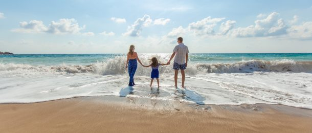 Parents holding hands with daughter wading in the ocean.
